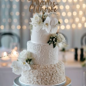 hand piped lace and ruffle wedding cake with fresh flowers