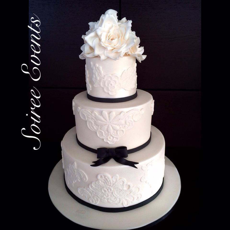 white sugar lace cake with black trim and sugar roses